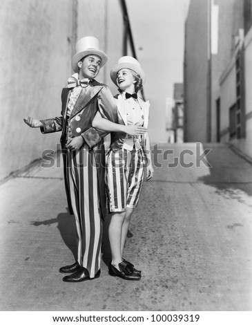 Profile of a young man and a young woman standing with arm in arm in a costume - stock photo