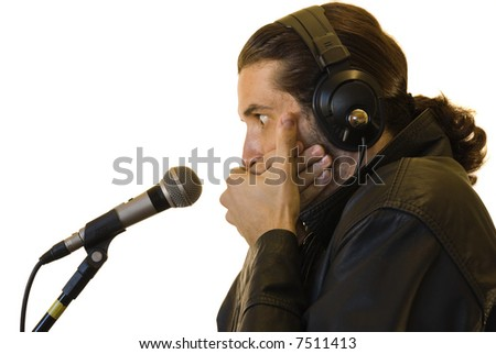Profile of a young man in a leather jacket, covering his mouth with both hands in front of a microphone - surprised face.
