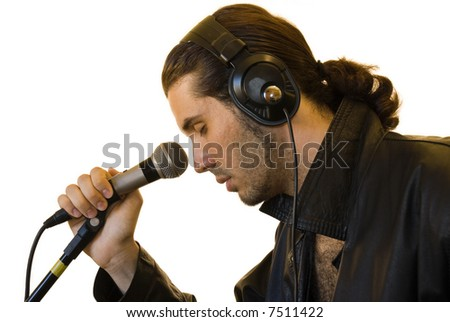 Profile of a young man in a leather jacket singing in a romantic way in a microphone.
