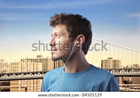 Profile of a young man listening to music with cityscape in the background - stock photo
