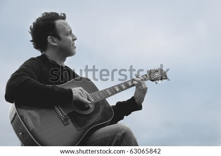 profile of a young  man playing guitar isolated on a cloudscape background , Quebec, Canada - duotones image - stock photo