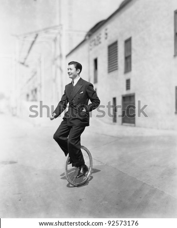 Profile of a young man riding a unicycle - stock photo