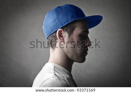 Profile of a young man wearing a cap - stock photo