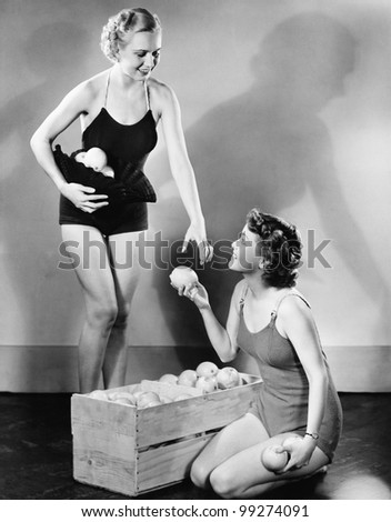 Profile of a young woman giving fruits to her friend - stock photo