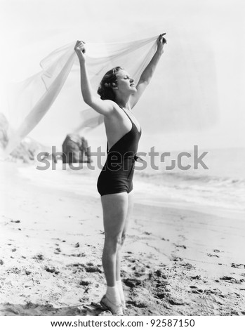 Profile of a young woman holding up a sarong at the beach - stock photo