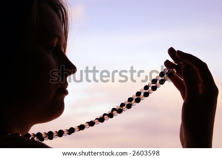 Profile of a young woman looking at beads - stock photo
