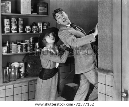 Profile of a young woman pushing out a young man from a domestic kitchen - stock photo