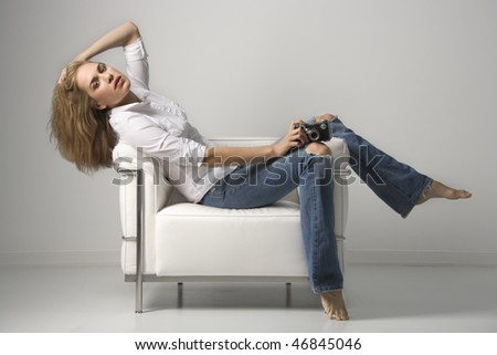 Profile of a young woman seated on a chair holding a camera. Horizontal shot. - stock photo