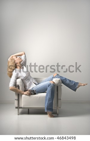Profile of a young woman seated on a chair holding a camera. Vertical shot. Isolated on white. - stock photo