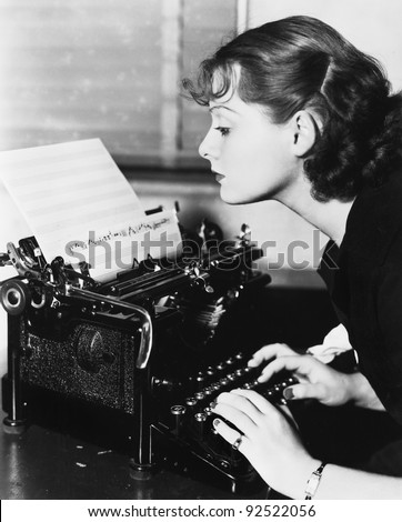 Profile of a young woman typing musical notes with a typewriter - stock photo