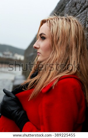Profile of a young woman wearing a red coat leaning against an old stone wall - stock photo