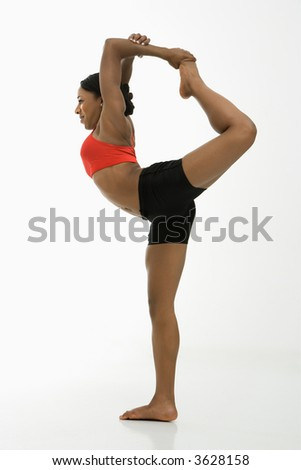 Profile of African American woman in Lord of the Dance Yoga position. - stock photo