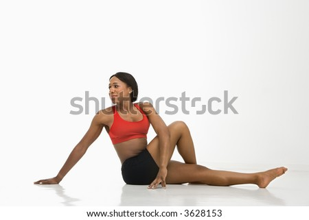 Profile of African American young adult woman stretching on floor. - stock photo