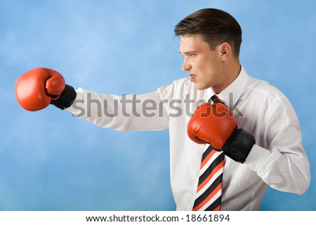 Profile of aggressive businessman in red boxing gloves stretching his arm out - stock photo