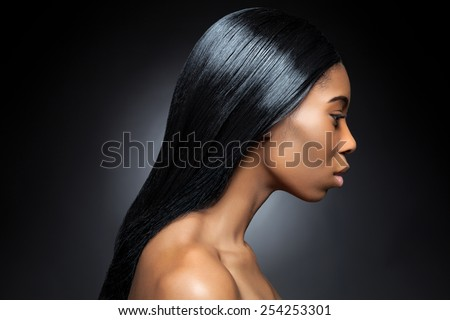 Profile of an young black beauty with long straight and shiny hair
