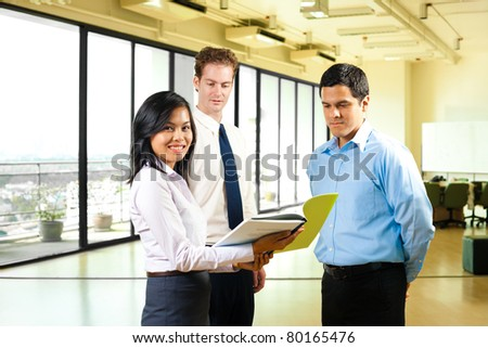 Profile of attractive Asian female team leader in business attire looking at camera, standing and sharing documents with Hispanic, Caucasian male coworkers in bright office. Horizontal