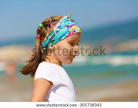Profile of baby girl with a bandanna on his head on a blurred background of blue sky and sea. Hot sunny summer day. Selective focus. - stock photo