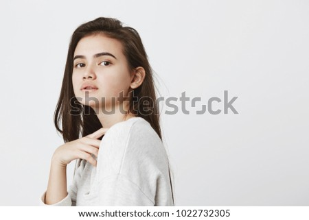 Profile of beautiful girl with dark loose hair keeping dressed casually, looking at camera with dark appealing eyes, posing against gray background. Beauty, youth and tenderness