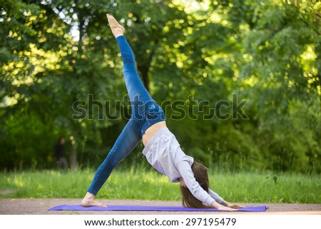 Profile of beautiful sporty young woman working out on blue mat on the street in park alley, doing eka pada adho mukha svanasana, one legged downward-facing dog pose, full length - stock photo