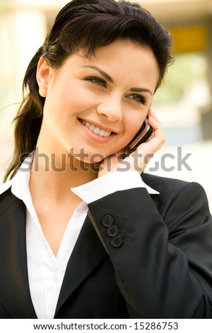 Profile of beautiful woman calling by phone outdoor