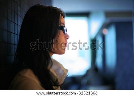 Profile of beautiful young brunette woman indoors. Shallow DOF.
