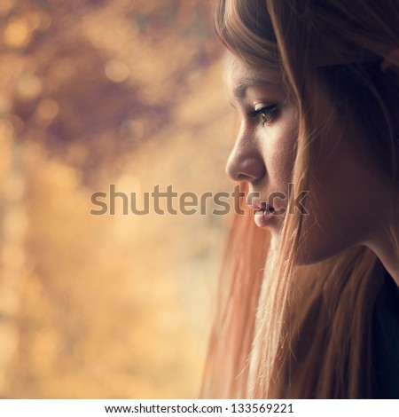 Profile of beautiful young girl outdoors - stock photo