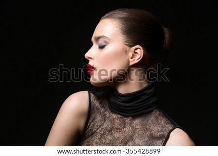 Profile of beautiful young woman in lace top with red lips. Over black background. Copy space. - stock photo