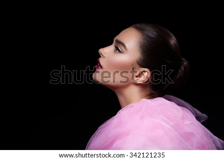 Profile of beautiful young woman in pink lace fluffy collar looking up over black background - stock photo