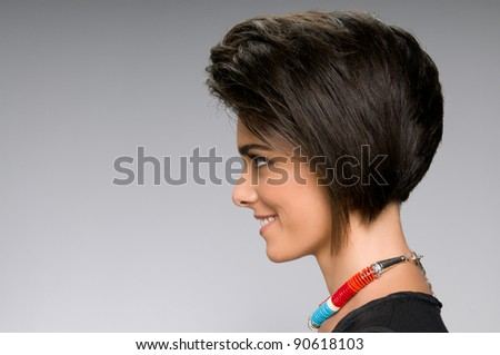 Profile of beautiful young woman with straight short hairstyle on gray background - stock photo