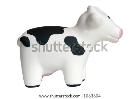Profile of black & white toy cow, isolated on white background.