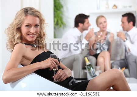 Profile of blond woman sitting holding champagne glass friends in background - stock photo