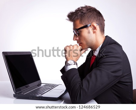 Profile of business man sitting at desk working on laptop computer - stock photo