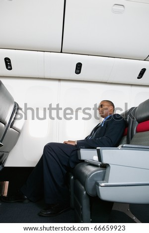 Profile of businessman on airplane