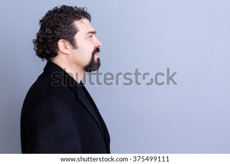 Profile of calm handsome dark haired and bearded middle aged man wearing black shirt and blazer over gray background with copy space - stock photo