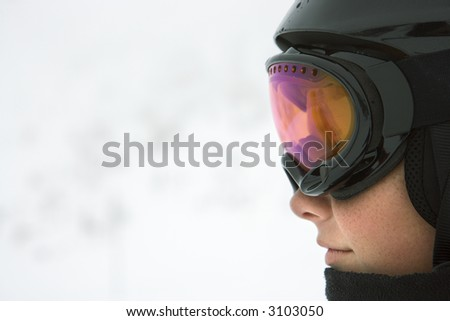 Profile of Caucasian teenage boy skier wearing helmet and goggles at ski resort on mountain Whistler, British Columbia, Canada. - stock photo
