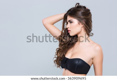 Profile of charming alluring attractive young woman in black bra posing over grey background  - stock photo