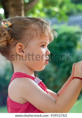 Profile of cute girl looking at it in the park - stock photo