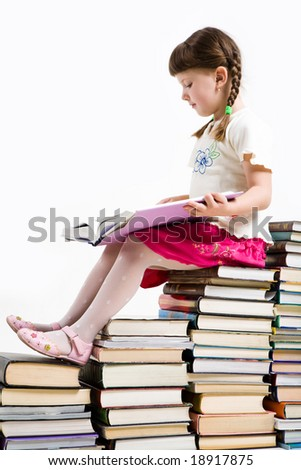 Profile of diligent pupil sitting on pile of books and reading one of them - stock photo