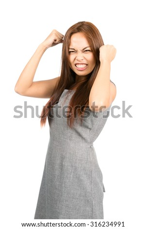 Profile of disappointed Asian girl with light brown hair, clenched teeth, balled fists, frowning during temper tantrum, fed up, annoyed and irritated. Thai national of Chinese origin. Vertical - stock photo