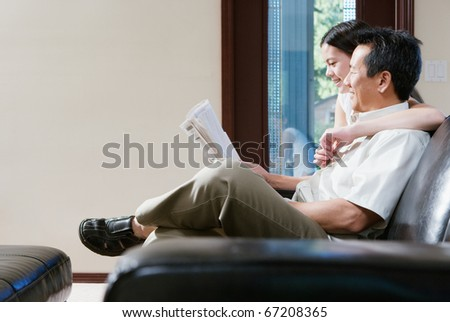Profile of father and daughter sitting on couch reading newspaper - stock photo