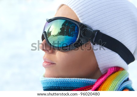 Profile of female skier wearing ski glasses in the mountains - stock photo