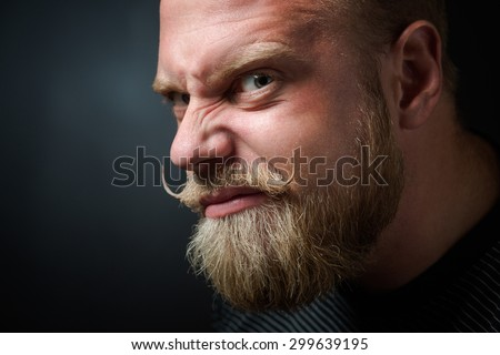 Profile of frightening bearded man on black. Man with serious glance looking with wickedness and narrowing his eyes. - stock photo