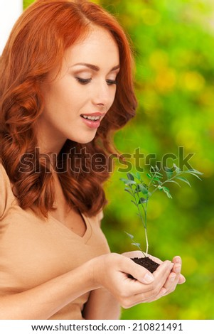 Profile of girl holding little plant in her hands. Woman's hands holding soil with plant and smiling - stock photo