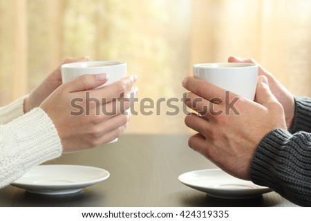 Profile of hands of a couple holding coffee cups over a table in winter in an apartment with a window in the background - stock photo