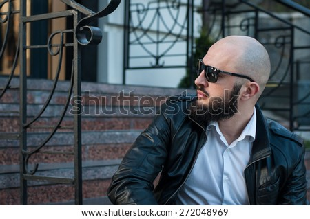 profile of handsome bearded man sitting on stairs - stock photo