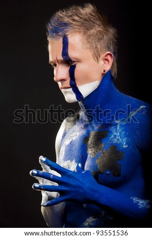 profile of handsome caucasian man with body-art mozaic painting and face decoration standing against black background: part of body-art project - stock photo