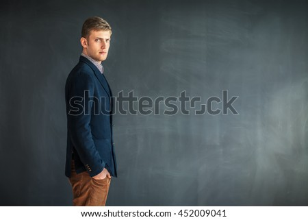 Profile of handsome man standing against grey wall background with copy space - stock photo
