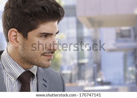 Profile of handsome young businessman outdoors. - stock photo