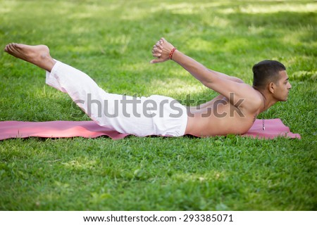 Profile of Indian young man with tattoo in white linen clothes practicing yoga, fitness, pilates in park, doing back extension exercise, shalabhasana, Locust Pose, Double Leg Kicks, full length - stock photo