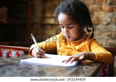 Profile of little African girl writing  at home. - stock photo